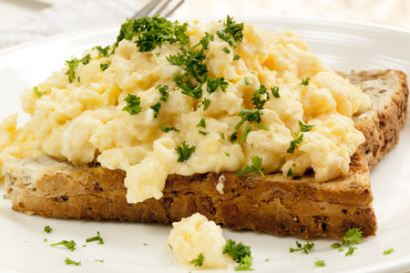 scrambled eggs: Scrambled eggs on toast, garnished with parsley.