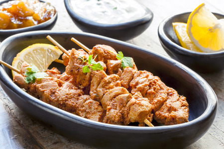 Tandoori Hähnchenspieße, serviert mit Joghurt, Zitronenscheiben und Mango-Chutney.