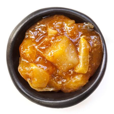 chutney: Mango chutney in small black dish, isolated on white.