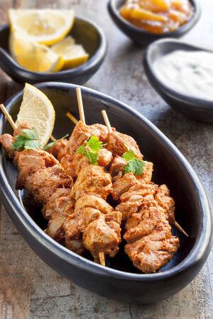 tandoori chicken: Tandoori chicken skewers, served with yogurt, lemon wedges and mango chutney.