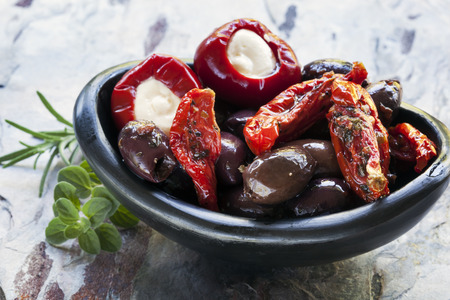 italian cusine: Antipasto in black bowl.  Olives, sundried tomatoes, and mozzarella stuffed bell peppers.