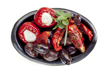 italian cusine: Dish of antipasto, isolated on white. Black olives, sundried tomatoes, and mozzarella stuffed bell peppers.
