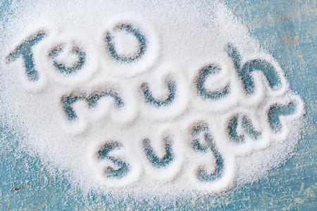 The words too much sugar written in sugar grains.  Overhead view.