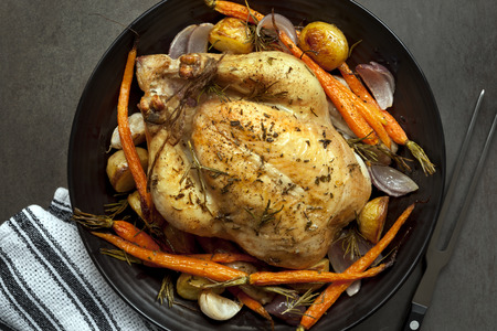 roast chicken: Roasted chicken dinner with vegetables and herbs.  Overhead view.