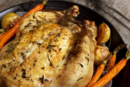Roasted chicken dinner with vegetables and herbs.  photo