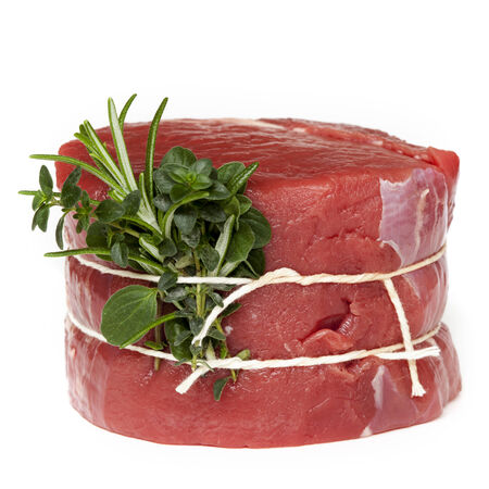mignon: Raw beef steak tied with fresh herbs, isolated on white.