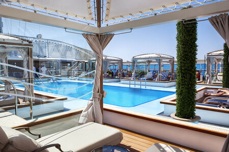 Pool deck with cabanas on board luxury cruise ship.