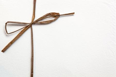 Arco de cuerda sobre papel blanco con textura.