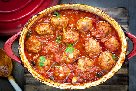 mincemeat: Meatballs casserole in red iron crock pot. Stock Photo