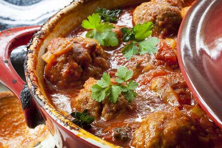 casserole: Meatballs casserole in red iron crock pot. Stock Photo