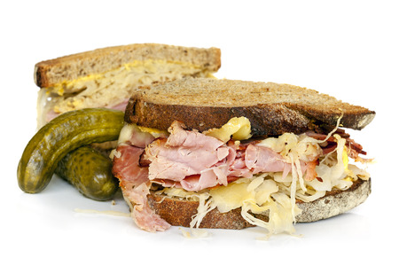 Reuben sandwich isolated on white, with dill pickles.