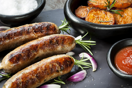cooked sausage: Grilled sausages with rosemary, sweet potato fries, and red onion.