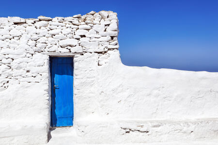 whitewashed: Blue door in whitewashed wall on Mykonos, Greece.