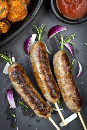 Grilled sausages with rosemary, sweet potato fries, and red onion. photo