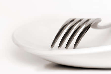 dinnerware: White plate with fork.  Shallow depth of field. Stock Photo