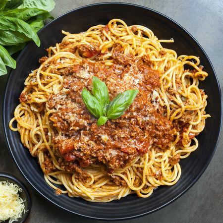 comida italiana: Espagueti bolo��s en plato de servir negro, con albahaca fresca y queso parmesano.