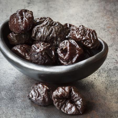 Prunes in black bowl, over dark slate.