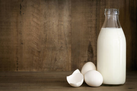 cracked egg: Bottle of milk with white eggs and eggshells.  Grunge effects. Stock Photo