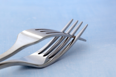 entwined: Two forks entwined, over pastel blue background. Stock Photo