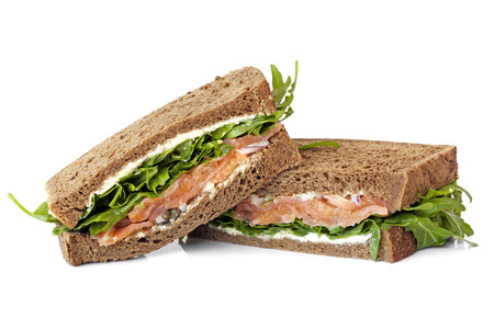 Smoked salmon sandwich on rye with arugula, cream cheese and capers.  Isolated. Stock Photo