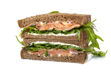 salmon ahumado: Sándwich de salmón ahumado con pan de centeno con rúcula, queso crema y alcaparras. Aislados. Foto de archivo
