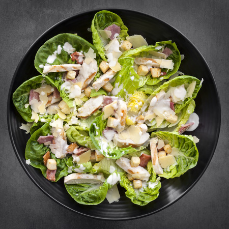 Chicken Caesar salad on black plate over slate.  Overhead view.