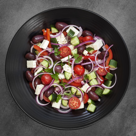 Greek salad on black plate over dark slate.  Overhead view. Фото со стока