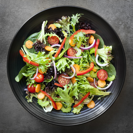 Garden salad in black bowl.  Top view, over slate.