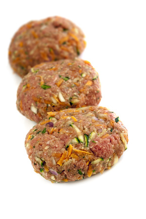 lowfat: Healthy hamburger patties, isolated on white.  Raw beef mixed with grated vegetables, including carrot and zucchini or courgette.