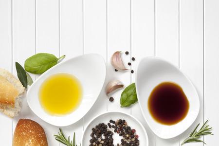 aceite de oliva: Aceite y vinagre fondo de alimentos, con pan fresco, pimienta y hierbas sobre panel de madera blanca. Foto de archivo