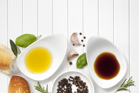 Oil and vinegar food background, with fresh bread, peppercorns and herbs over white wood panel. Stockfoto