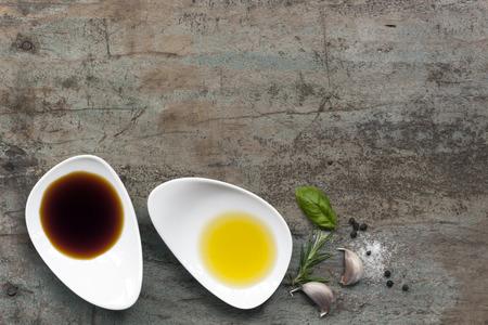 油と酢食品背景、胡椒、塩、ニンニク、ローズマリー、グランジ木上で。