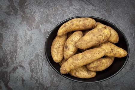 unwashed: Unwashed fingerling o Kipfler potaotes prime in un piatto nero su sfondo scuro di ardesia.