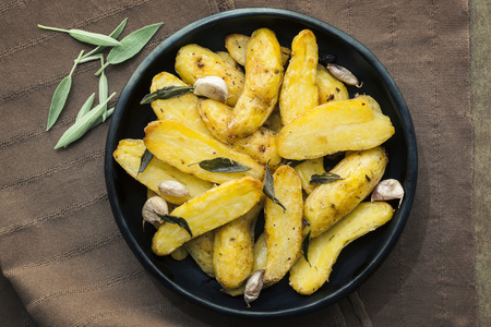 fingerling: Roasted fingerling or kipfler potatoes, with sage leaves.  Black dish, overhead view. Stock Photo