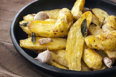 fingerling: Roasted fingerling or kipfler potatoes, with sage leaves, in black dish.