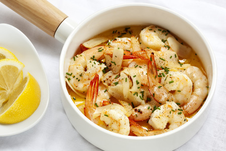 chives: Shrimp with garlic butter, lemon and chives, in white serving pan. Stock Photo