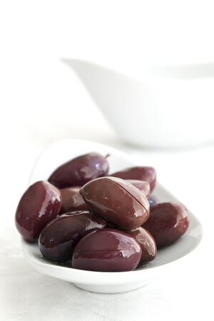 black olives: Black olives in small white dish.