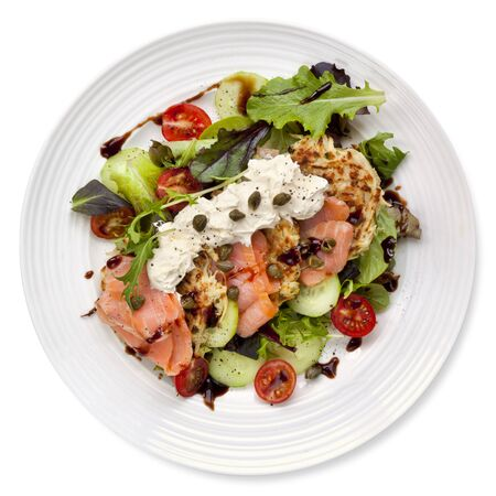 seafood salad: Smoked salmon salad with potato rosti and creme fraiche.  Overhead view, isolated on white.