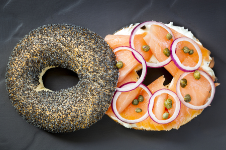 overhead view: Bagel with smoked salmon, cream cheese, capers and red onion.  Overhead view, on dark slate.