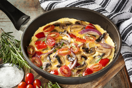 Cooking omelet in frypan, with mushrooms, cherry tomatoes, onions, capsicum and herbs.