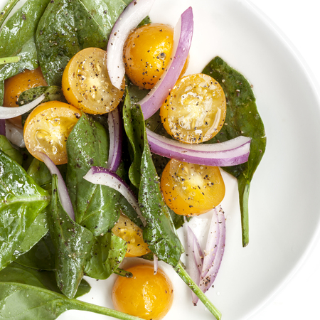 baby spinach: Spinach salad with yellow cherry tomatoes and red onion.  Overhead view, on white plate. Stock Photo