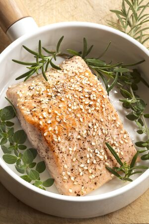 white sesame seeds: Salmon fillet with sesame seeds and herbs.  In white frypan. Stock Photo