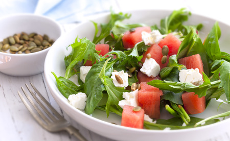 Wassermelonensalat mit Feta-Käse, gerösteten Kürbiskernen, Rucola, Spinat und Minze.