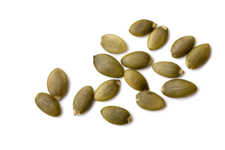 scattered on white background: Pumpkin seeds or pepitas, isolated on white background.  Overhead view. Stock Photo