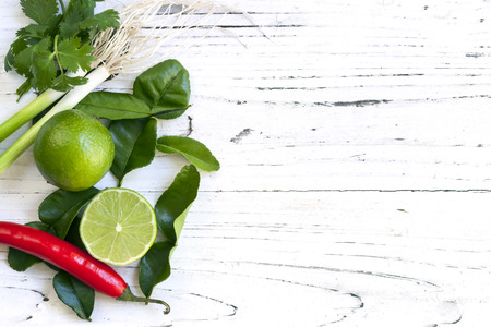 limes: Kaffir lime leaves, fruit, coriander or cilantro, red chilli and green onions over white distressed wooden background. Overhead view.