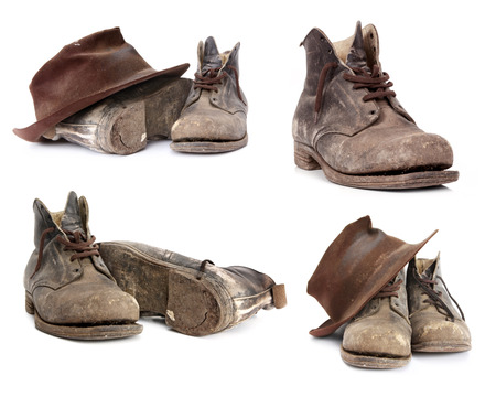 old leather: Old work boots and battered hat.  Collection isolated on white.