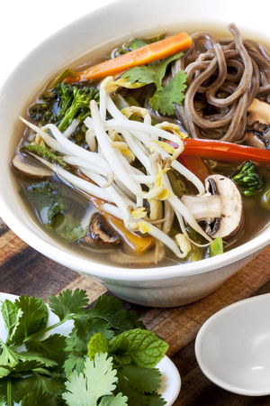 soba noodles: Hot and sour vegetable soup with soba noodles and bean sprouts.  Garnished with mint and coriander or cilantro.