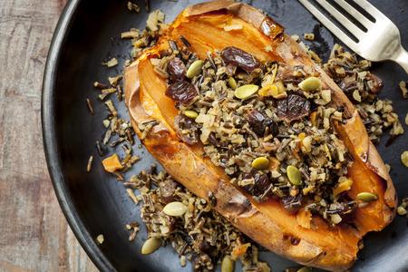 Gebackene süße Kartoffel oder Süßkartoffel, mit Wildreis, pepitas, und Preiselbeeren gestopft.