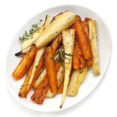 roast: Roasted parsnips and carrots garnished with rosemary and thyme.  White plate, overhead view. Stock Photo
