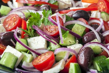 Griechischer Salat in Full-Frame. Schwarze Oliven, Feta-Käse, Gurken, Tomaten, roten Zwiebeln und Kräutern. Lizenzfreie Bilder